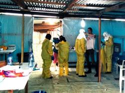 © Tim Shenk/MSF Brett Adamson, coordinateur pour MSF aide un soignant qui se prépare à entrer dans la zone à haut risque du camp ELWA 3 à Monrovia (Liberia)