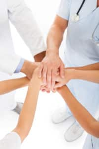 Close-up Photo Of Doctors Stacking Hand With Coworkers