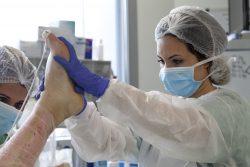 """©Natacha Soury Zineb surélève la jambe de la patiente afin que Karine, aide-soignante, puisse enlever la totalité du """"voile de mariée"""". L'équipe optera par la suite pour la pause de tulle gras."""