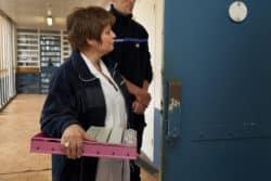 l'infirmière distribue les médicaments à la porte des cellules, toujours sous l'oeil du surveillant.