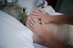 Charlotte, aide-soignante, masse une patiente. La toilette est un moment clef