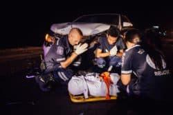 Une équipe de Vientiane Rescue fait une prière après avoir enveloppé le corps sans vie d'un accidenté de la route dans un tissu blanc