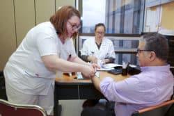 Caroline Juliard Albany, infirmière, met un bracelet d'identification et fera dans la foulée une prise de sang, pendant la consultation avec le médecin, Lucie Cabrejo