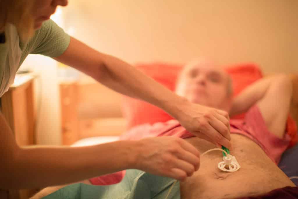 Un autre patient de l'HAD, dont Elodie s'occupe, est atteint d'un cancer gastrique. Ce matin, il se plaint de douleurs au ventre. L'infirmière l'interroge donc sur son alimentation, sur son transit, lui palpe le ventre. Elle est également présente pour lui refaire son pansement de gastrostomie. © Pascal Vo