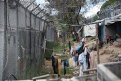 Des migrants font sécher leur linge sur des fils tendus entre leurs abris de fortune et les grillages délimitant le Hotspot de Moria