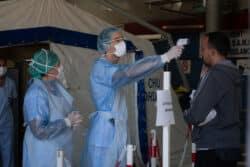 Dans le poste médical avancé, au CHU de Bordeaux, prise de température d'un patient ne présentant pas de signes cliniques majeurs. Il est vu par des infirmiers d'accueil et d'orientation au niveau de l'espace d'attente