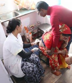 Cette femme suivie pour un furoncle très douloureux au bas du dos, est soutenue par son mari pendant que Son nettoie avant de refaire le pansement