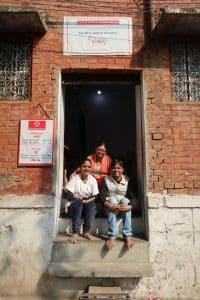 L'entrée au dispensaire : à gauche, Sont, formée par Céline aux soins infirmiers; à droite, Nitin et, au centre, Sonali, qui donne un coup de main à l'équipe et s'occupe du cahier d'enregistrement des soins